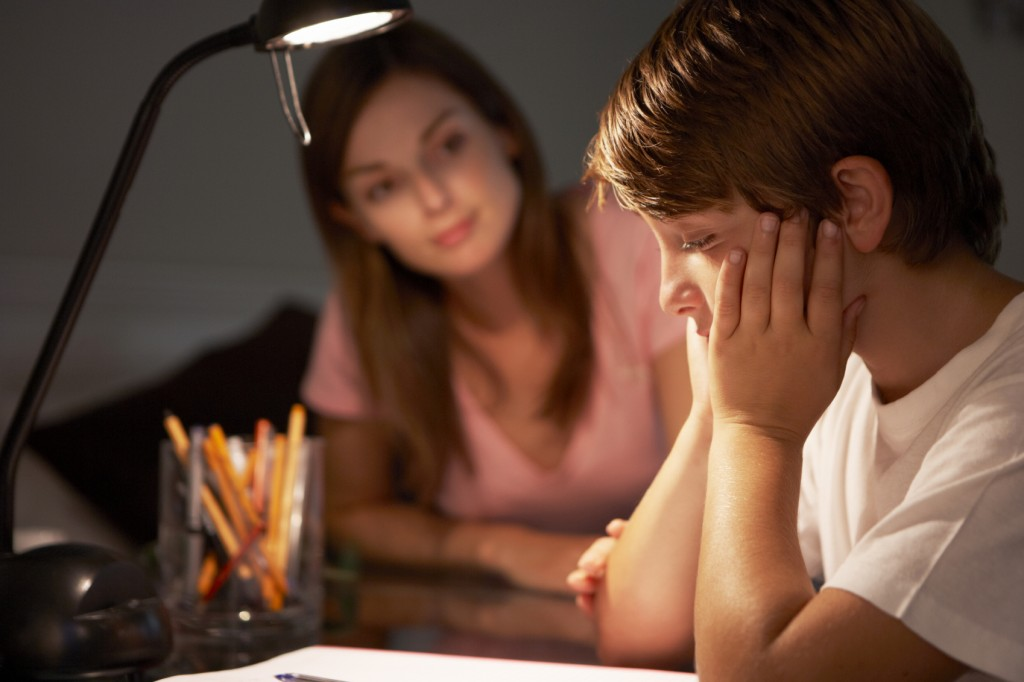 Teenage Sister Helping Stressed Younger Brother With Studies At Desk In Bedroom In Evening
